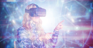 Composite image of pretty casual worker using oculus rift. Pretty casual worker using oculus rift against black background with glowing network Royalty Free Stock Image