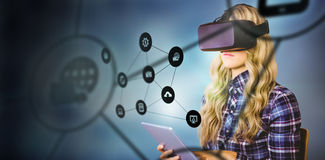 Composite image of pretty casual worker using oculus rift. Pretty casual worker using oculus rift against smartphone apps icons Stock Images