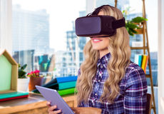 Composite image of pretty casual worker using oculus rift. Pretty casual worker using oculus rift against view of a business desk Royalty Free Stock Image