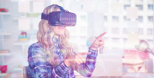 Composite image of pretty casual worker using oculus rift. Pretty casual worker using oculus rift against view of office interior with sticky note on window Royalty Free Stock Photo