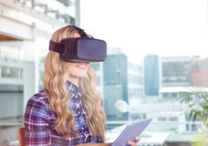 Composite image of pretty casual worker using oculus rift. Pretty casual worker using oculus rift against working desk in a office Royalty Free Stock Photos