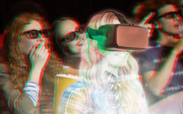 Composite image of pretty casual worker using oculus rift. Pretty casual worker using oculus rift against young friends watching a 3d film Royalty Free Stock Images
