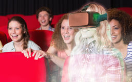 Composite image of pretty casual worker using oculus rift. Pretty casual worker using oculus rift against young friends watching a film Royalty Free Stock Images