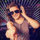 Composite image of pretty female dj playing music. Pretty female DJ playing music against flying colours Stock Photos