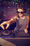 Composite image of pretty female dj playing music. Pretty female DJ playing music against flying colours Royalty Free Stock Photo