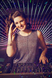 Composite image of pretty female dj playing music. Pretty female DJ playing music against flying colours Stock Image