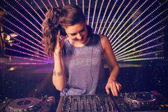 Composite image of pretty female dj playing music. Pretty female DJ playing music against flying colours Royalty Free Stock Images