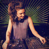 Composite image of pretty female dj playing music. Pretty female DJ playing music against flying colours Stock Images