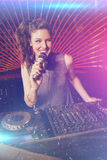 Composite image of pretty female dj playing music. Pretty female DJ playing music against flying colours Royalty Free Stock Image