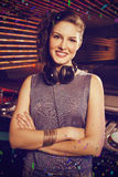 Composite image of pretty female dj standing with arms crossed Stock Photography