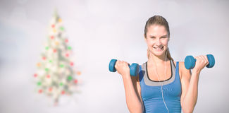 Composite image of pretty fit woman. Pretty fit woman against blurry christmas tree in room Stock Photography
