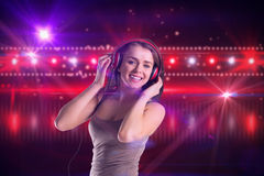 Composite image of pretty girl listening to music Royalty Free Stock Photo