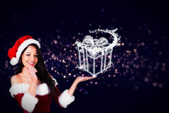Composite image of pretty girl presenting in santa outfit Stock Photography