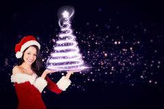 Composite image of pretty girl presenting in santa outfit Stock Photos