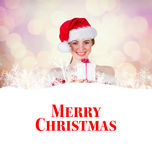 Composite image of pretty girl in santa costume holding gift box. Pretty girl in santa costume holding gift box against glowing christmas background Royalty Free Stock Photography