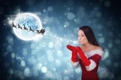 Composite image of pretty girl in santa outfit blowing Royalty Free Stock Photo
