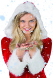 Composite image of pretty girl in santa outfit with hands out Royalty Free Stock Photos