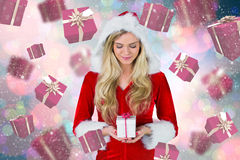 Composite image of pretty girl in santa outfit holding gift Stock Photography