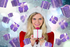 Composite image of pretty girl in santa outfit holding gift Stock Photo