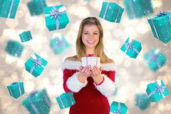Composite image of pretty girl in santa outfit holding gift Stock Photos