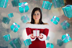 Composite image of pretty girl in santa outfit holding gift Stock Images