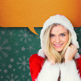 Composite image of pretty girl smiling in santa outfit Stock Photo