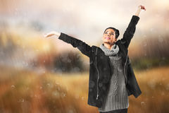 Composite image of pretty girl in winter jumper lifting arms Royalty Free Stock Photo