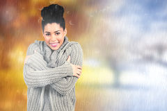 Composite image of pretty girl in winter jumper looking at camera Royalty Free Stock Photography