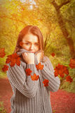 Composite image of pretty girl in winter jumper looking at camera Stock Image