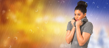 Composite image of pretty girl in winter jumper shivering. Pretty girl in winter jumper shivering against autumn changing to winter Royalty Free Stock Image