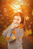Composite image of pretty girl in winter jumper smiling at camera Royalty Free Stock Image