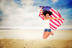Composite image of pretty girl wrapped in american flag jumping and smiling at camera stock photography