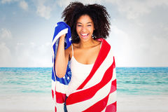 Composite image of pretty girl wrapped in american flag smiling at camera Royalty Free Stock Photography