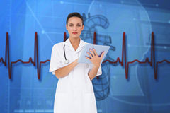 Composite image of pretty nurse using tablet pc Royalty Free Stock Photography