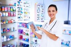 Composite image of pretty nurse using tablet pc Stock Photo