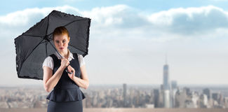 Composite image of pretty redhead businesswoman holding umbrella Royalty Free Stock Photography