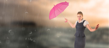 Composite image of pretty redhead businesswoman holding umbrella Royalty Free Stock Images