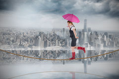 Composite image of pretty redhead businesswoman holding umbrella on tightrope Royalty Free Stock Photos