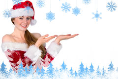 Composite image of pretty redhead in santa outfit presenting with hands Royalty Free Stock Photos