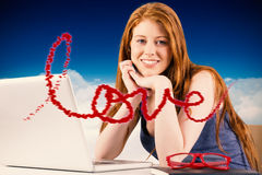 Composite image of pretty redhead working on laptop Royalty Free Stock Photo