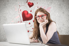 Composite image of pretty redhead working on laptop Royalty Free Stock Photos