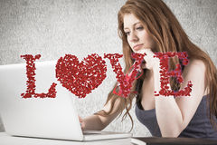 Composite image of pretty redhead working on laptop Stock Photos