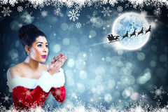 Composite image of pretty santa girl blowing over her hands. Pretty santa girl blowing over her hands against fir tree forest and snowflakes Stock Photo