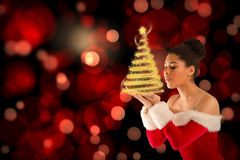 Composite image of pretty santa girl blowing over her hands Royalty Free Stock Photography