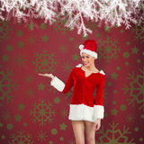 Composite image of pretty santa girl presenting with hand Royalty Free Stock Images