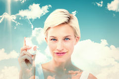 Composite image of pretty woman holding inhaler smiling at camera Royalty Free Stock Photo