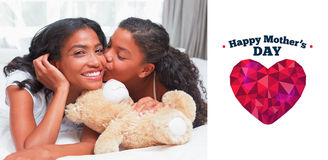 Composite image of pretty woman lying on bed with her daughter kissing cheek Stock Image