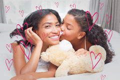 Composite image of pretty woman lying on bed with her daughter kissing cheek Royalty Free Stock Photo