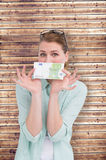 Composite image of pretty woman showing an one hundred euro note Stock Photo