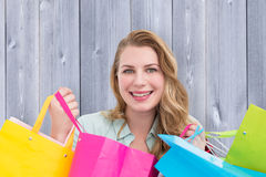 Composite image of pretty woman smiling at the camera with shopping bags Royalty Free Stock Photo